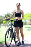 Young fitness woman with bicycle