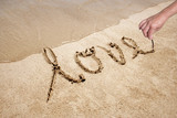 Love handwritten in sand for natural poster