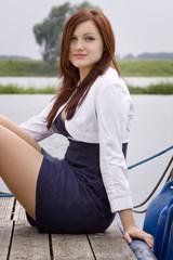 Frau sitzt auf einem Steg im Yachthafen