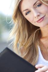 Beautiful Young Blond Woman Reading Folder or Menu