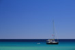 Sailboat on a clear blue sea under a cloudless blue sky