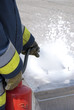 Firefighter using foam fire extinguisher