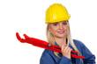Frau in blauer Arbeits Kleidung mit Rohrzange