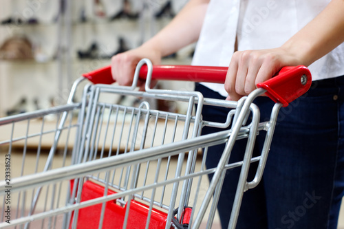 Woman pushing shopping cart in shoe store