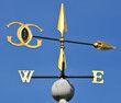 Golden wind vane against a clear blue sky