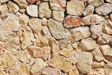 Fragment of a wall made of rough mixed stones