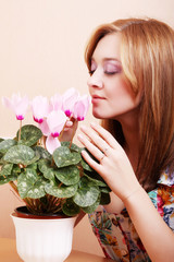 Girl sniffing flowers cyclamen
