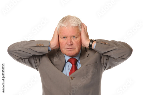 Successful mature businessman covering ears
