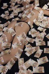 A woman lying on the bed is covered with fifty Euro banknotes