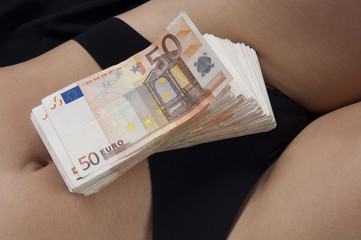 A bundle of fifty euro notes on the crotch of a girl escort