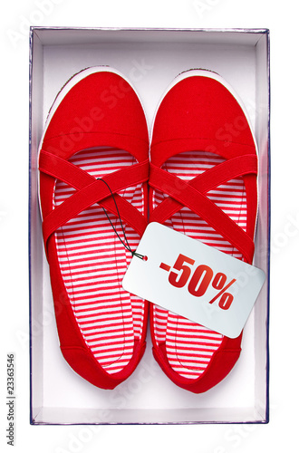 Female red shoes with price tag in box, isolated on white