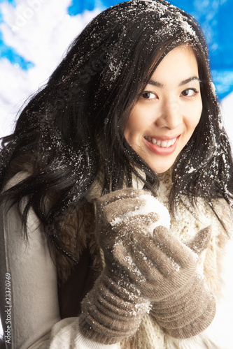 Young Woman Wearing Warm Winter Clothes Holding Snowball In Stud