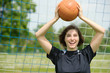 Attraktive junge,brünette Frau fängt Ball im Tor