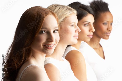 Portrait Of Four Attractive Young Women In Studio Standing In Li