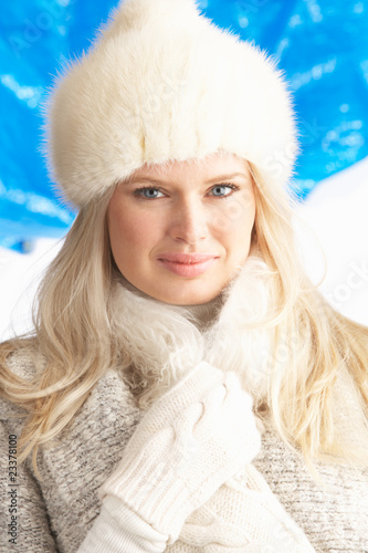 Young Woman Wearing Warm Winter Clothes And Fur Hat In Studio