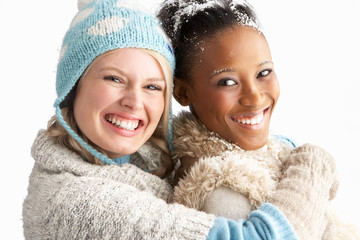 Two Young Women Wearing Warm Winter Clothes Holding Snowball In