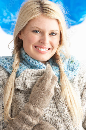 Pretty Young Woman Wearing Warm Winter Clothes In Studio