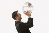 Smiling Businessman Holding Globe Like a Basketball - Isolated