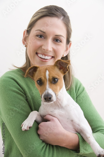 Attractive Young Woman Holding A Dog And Smiling