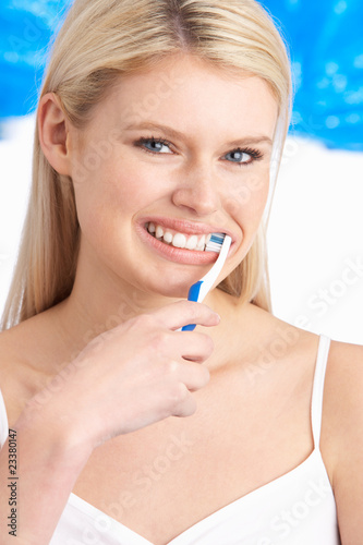 Young Woman Brushing Teeth In Studio