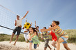 canvas print picture - Group Of Teenage Friends Playing Volleyball On Beach