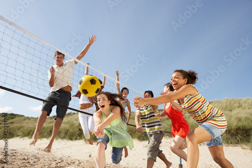 canvas print picture Group Of Teenage Friends Playing Volleyball On Beach