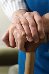 hands  of a senior woman on cane