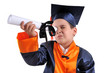 Elementary boy wearing graduation cap and gown shows his diploma