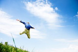 Businessman jumping on a green meadow with copyspace