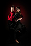 Young couple passion flamenco dancing on red light background.