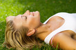 Beautiful healthy Young Woman lying on the green grass