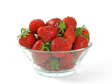 fresh and juicy strawberries on glass bowl over white