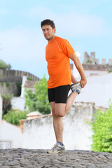 middle age man making stretching movements before run