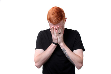 Redhair teenager closes his face with hands