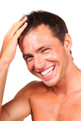 Closeup of a happy young man touching his hair