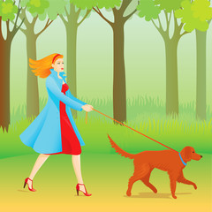 Beautiful ginger woman walking her dog in a park