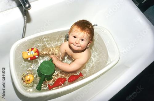 Baby planscht in seiner Babybadewanne mit Plastikspielzeug