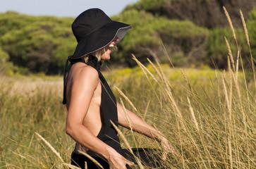 Mujer en el campo con vestido y sombrero negro