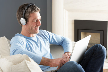 Man Using Laptop Wearing Headphones Relaxing Sitting On Sofa At