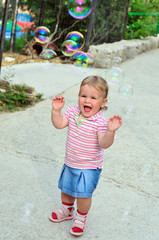 girl catching soap bubbles