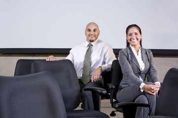 Hispanic business people sitting on office chairs