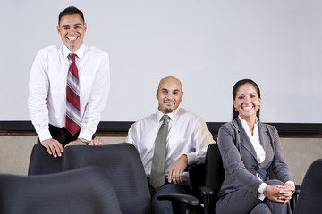 Three Hispanic business colleagues in boardroom