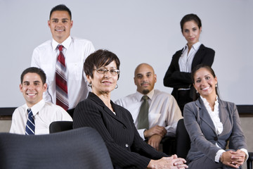 Mature Hispanic businesswoman leading office group