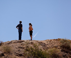 Hikers in desert point to aircraft trail