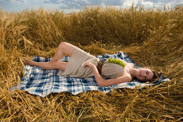 Beautiful slavonic girl on picnic in wheat field with grapes