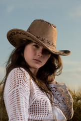 Beautiful slavonic girl in cowboy clothes pose in wheat field