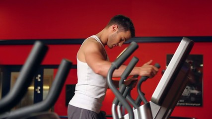 Handsome sporty man is exercising in gym centre