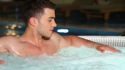 Handsome man is relaxing in jacuzzi