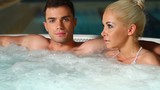 Attactive couple are relaxing in jacuzzi poster