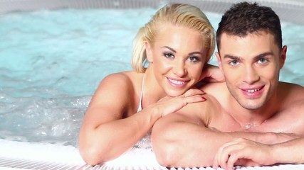 Attactive couple are relaxing in jacuzzi